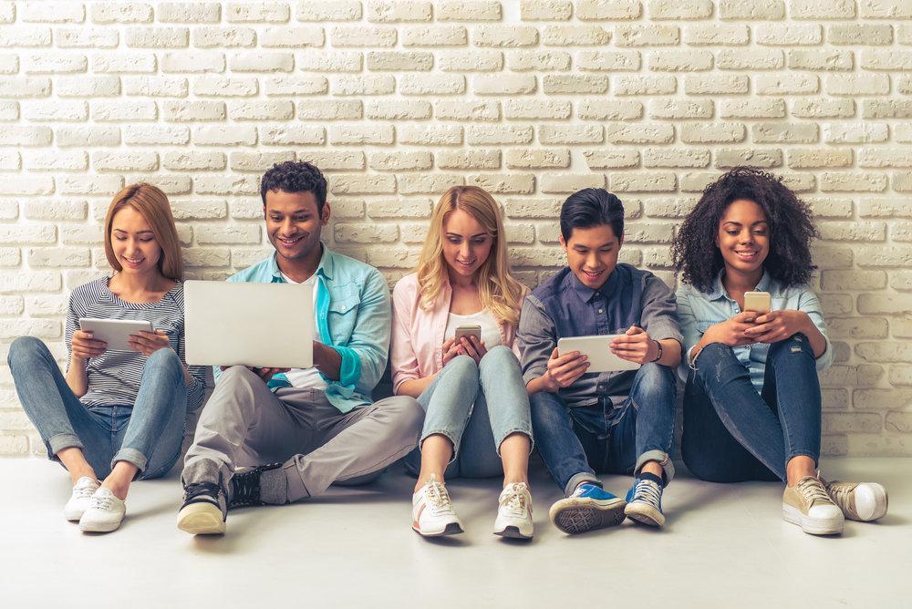 タブレット、ノートパソコン、スマホを見る若者