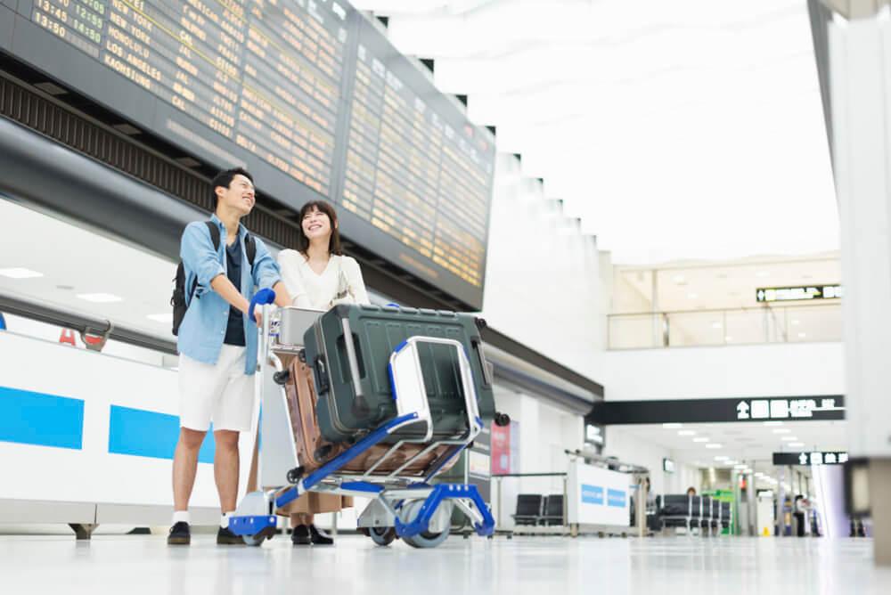 手荷物(スーツケース)のカートを押して空港を移動するカップル