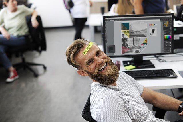 「BE HAPPY」という紙をおでこに貼ったビジネスマンとオフィス