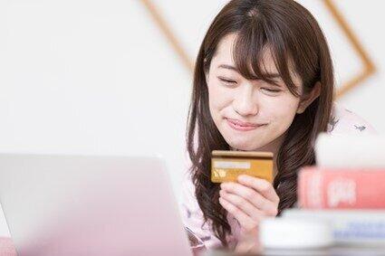 クレジットカードを見て微笑む女性